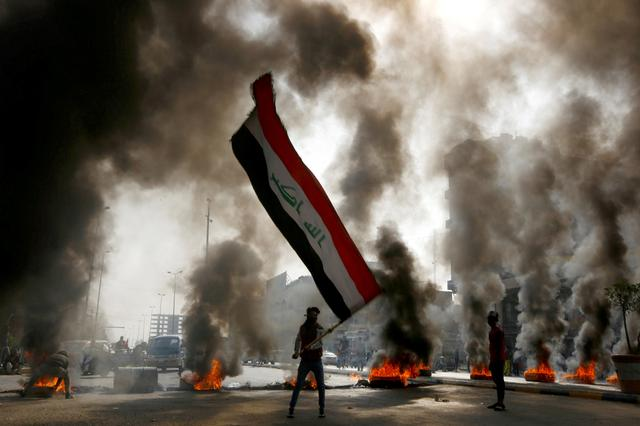 FILE PHOTO: A protester holds an Iraqi flag amid a cloud of smoke from burning tires during ongoing anti-government protests in Najaf, Iraq November 26, 2019. REUTERS/Alaa al-Marjani/File Photo