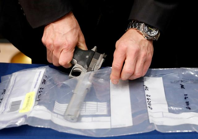 FILE PHOTO: A confiscated handgun is placed into an evidence bag during a news conference about a gun bust at New York City Police (NYPD) Headquarters in New York, U.S., May 24, 2018.  REUTERS/Brendan McDermid/File Photo