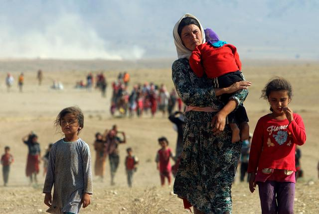 Displaced people from the minority Yazidi sect, fleeing violence from forces loyal to the Islamic State in Sinjar town, walk towards the Syrian border, on the outskirts of Sinjar mountain, near the Syrian border town of Elierbeh of Al-Hasakah Governorate, Iraq, August 11, 2014. Picture taken August 11, 2014. REUTERS/Rodi Said/File Photo