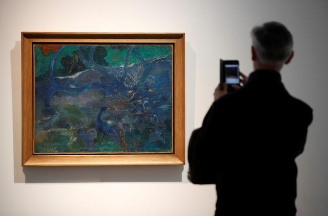 """FILE PHOTO: A man takes a picture of Paul Gaugin's """"Te Bourao II"""" (The Purao Tree) painting (1897) at Artcurial's auction house in Paris, France, October 3, 2019. REUTERS/ Christian Hartmann"""