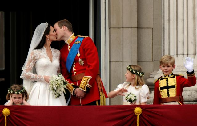 FILE PHOTO: Britain's Prince William and his wife Catherine, Duchess of Cambridge, kiss on the balcony at Buckingham Palace, watched by bridemaids Grace van Cutsem (L), Margarita Armstrong-Jones and pageboy Tom Pettifer, after their wedding in Westminster Abbey in London, Britain, April 29, 2011. REUTERS/Dylan Martinez