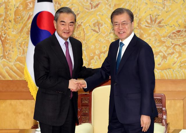 Chinese Foreign Minister Wang Yi is greeted by South Korean President Moon Jae-in during their meeting at the Presidential Blue House in Seoul, South Korea, December 5, 2019.   Yonhap via REUTERS