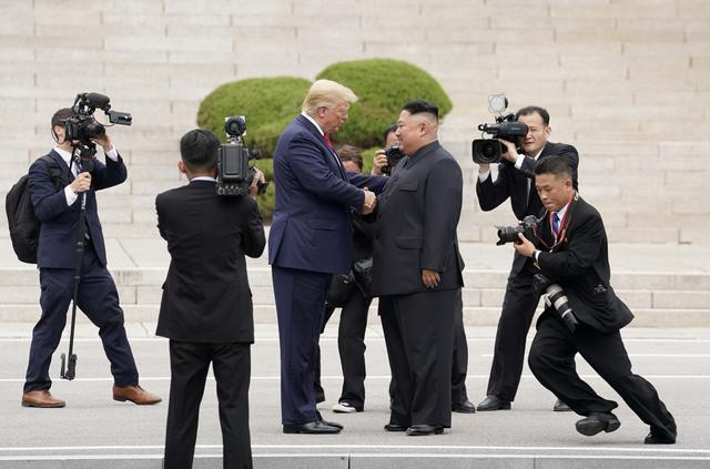 FILE PHOTO: U.S. President Donald Trump meets with North Korean leader Kim Jong Un at the demilitarized zone separating the two Koreas, in Panmunjom, South Korea, June 30, 2019. REUTERS/Kevin Lamarque/File Photo