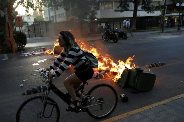 FILE PHOTO: A woman rides a bike next to a barricade during protest in Santiago, Chile December 3, 2019. REUTERS/Pablo Sanhueza