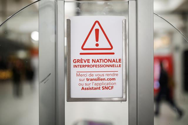 A placard is pictured on an electronic ticket checkpoint and access gate at the Gare du Nord railway station during a strike by French SNCF railway workers as part of a day of national strike and protests against French government's pensions reform plans, in Paris, France, December 5, 2019. The placard reads: National interprofessional strike. REUTERS/Benoit Tessier