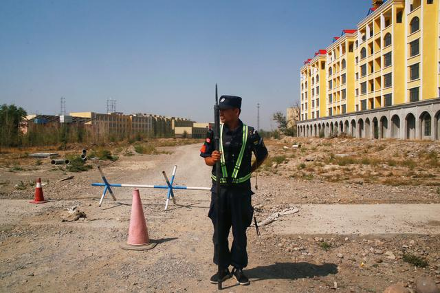 FILE PHOTO: A Chinese police officer takes his position by the road near what is officially called a vocational education centre in Yining in Xinjiang Uighur Autonomous Region, China September 4, 2018.  REUTERS/Thomas Peter/File Photo