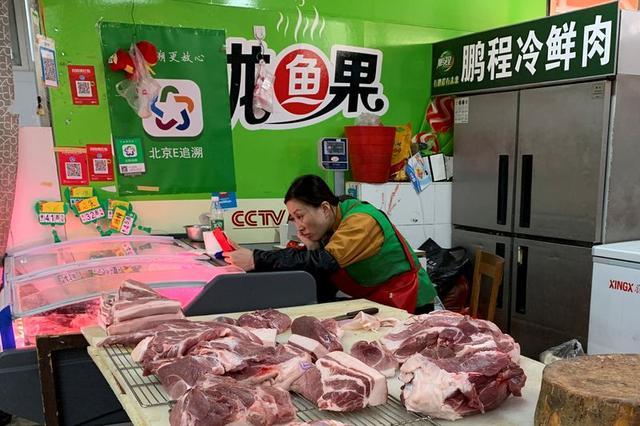 FILE PHOTO: A pork vendor checks her smartphone while waiting for customers at a market in Beijing, China, November 11, 2019.  REUTERS/Fang Nanlin
