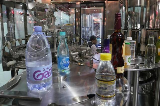 FILE PHOTO: A man sits behind a machine producing plastic bottles at the Canton Fair in Guangzhou, China October 16, 2017. REUTERS/Venus Wu
