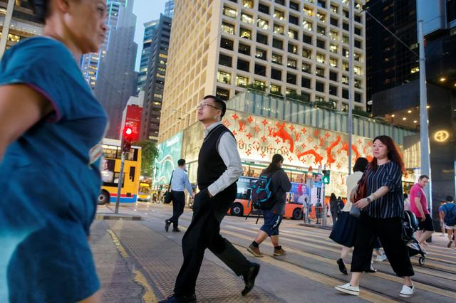 FILE PHOTO: People cross a street the Central business district in Hong Kong, China August 22, 2019. REUTERS/Thomas Peter