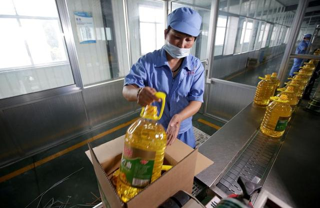 FILE PHOTO: A worker packs bottles of soybean oil made from imported U.S. soybeans at Liangyou Industry and Trade Co., Ltd in Qufu, Shandong province, China July 4, 2018. REUTERS/Jason Lee/File Photo