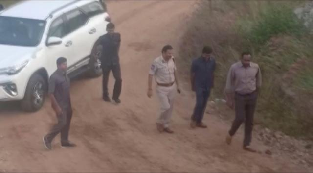 Still frame taken from December 6, 2019 video shows Cyberabad Police Commissioner V.C. Sajjanar and other police arriving at a spot where police shot dead four men suspected of raping a veterinary doctor, in Hyderabad, Telangana, India. ANI/via REUTERS TV