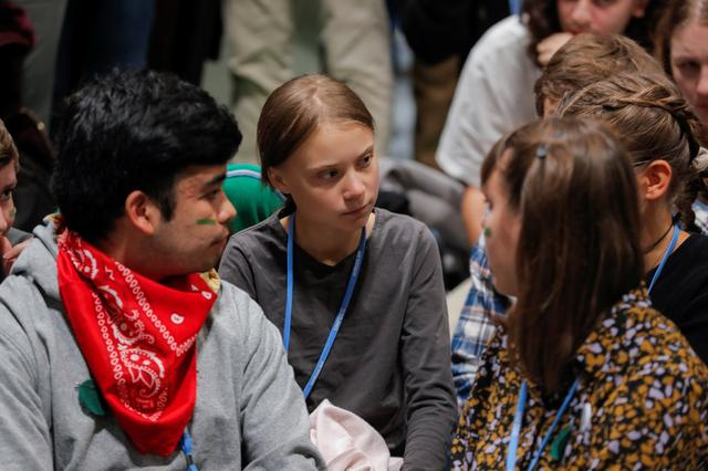 Climate change activist Greta Thunberg talks with participants at the COP25 in Madrid, Spain, December 6, 2019. REUTERS/Juan Medina