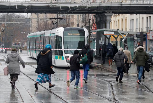 Commuters run to catch a RATP tramway as a strike by French SNCF railway and Paris transport network (RATP) workers continue to protest against French government's pensions reform plans, in Paris, France, December 6, 2019. REUTERS/Charles Platiau