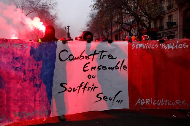 """Protesters hold a banner during a demonstration against French government's pensions reform plans in Paris as part of a day of national strike and protests in France, December 5, 2019. The slogan reads """"Fight together or suffer alone"""".  REUTERS/Gonzalo Fuentes"""