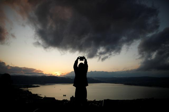 FILE PHOTO: A woman takes photos of Lake Suwa at dusk at Tateishi Park in Suwa, central Japan, November 11, 2019. REUTERS/Issei Kato