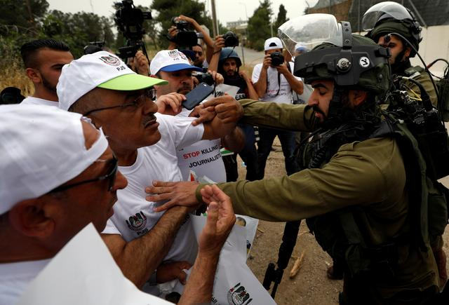 An Israeli soldier pushes back Palestinian journalists during a protest demanding freedom of the press, near Ramallah, in the occupied West Bank May 6, 2018. REUTERS/Mohamad Torokman