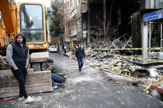 FILE PHOTO: People walk near a burnt bank, after protests against increased fuel prices, in Tehran, Iran November 20, 2019. Picture taken November 20, 2019. Nazanin Tabatabaee/WANA (West Asia News Agency) via REUTERS/File Photo