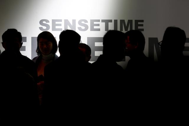 FILE PHOTO: Visitors walk past the stall of the artificial intelligence and facial recognition technology company Sensetime at the Security China 2018 exhibition on public safety and security in Beijing, China October 23, 2018.  REUTERS/Thomas Peter/File Photo