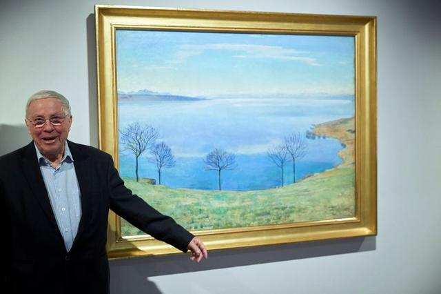 """Swiss billionaire and politician Christoph Blocher poses in front of a painting by Ferdinand Hodler """"Vue du Leman depuis Chexbres"""" after after a guided visit for the media of his collection at the Fondation Gianadda in Martigny, Switzerland, December 6, 2019.  REUTERS/Denis Balibouse"""