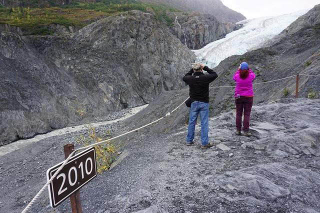 FILE PHOTO: A sign marks where the end of the Exit glacier was in 2010 near tourists taking photos in the Kenai Fjords National Park, Alaska, U.S. August 31, 2019.  REUTERS/Yereth Rosen