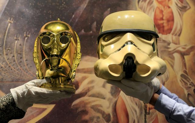 """Sotheby's employees hold a """"Return of the Jedi"""" promotional C-3PO Helmet 1983, estimated at £15,000-£25,000 created by George Lucas' visual effects company and a prototype of an Imperial Stormtrooper helmet 1976, estimated at £30,000-£60,000 created for the first """"Star Wars"""" film during a photocall at Sotheby's in London, Britain December 6, 2019. REUTERS/Thomas Mukoya"""