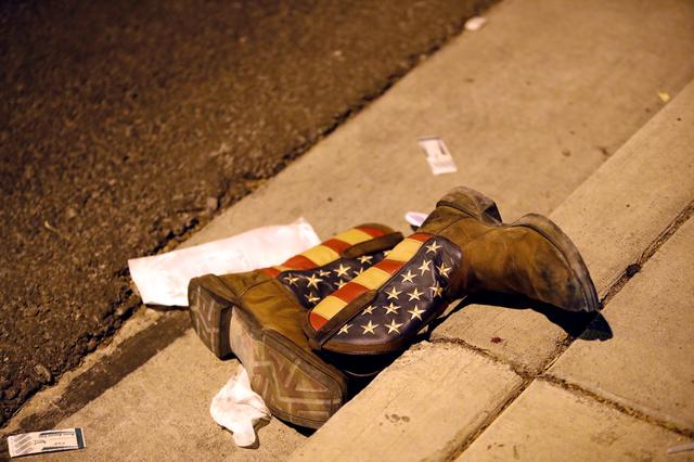 A pair of cowboy boots is shown in the street outside the concert venue after a mass shooting at a music festival on the Las Vegas Strip in Las Vegas, Nevada, U.S. October 1, 2017. REUTERS/Las Vegas Sun/Steve Marcus