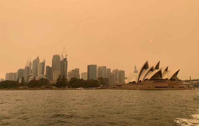 FILE PHOTO: The haze from bushfires obscures the sun setting above the Sydney Opera House in Sydney, Australia, December 6, 2019. REUTERS/John Mair