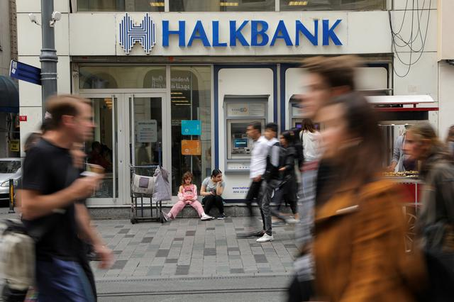 FILE PHOTO: People walk past by a branch of Halkbank in central Istanbul, Turkey, October 16, 2019. REUTERS/Huseyin Aldemir/File Photo