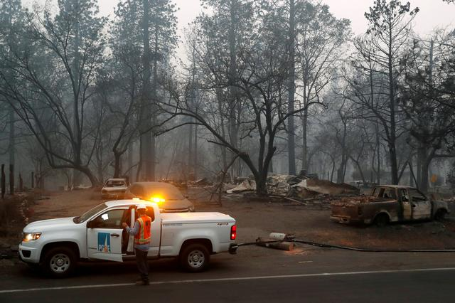 FILE PHOTO: Employees of Pacific Gas & Electric (PG&E) work in the aftermath of the Camp Fire in Paradise, California, U.S., November 14, 2018.  REUTERS/Terray Sylvester/File Photo