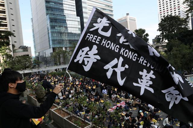 FILE PHOTO: An anti-government demonstrator holds a flag as people gather for a lunchtime protest at Chater Garden in Hong Kong, China, December 2, 2019. REUTERS/Leah Millis/File Photo