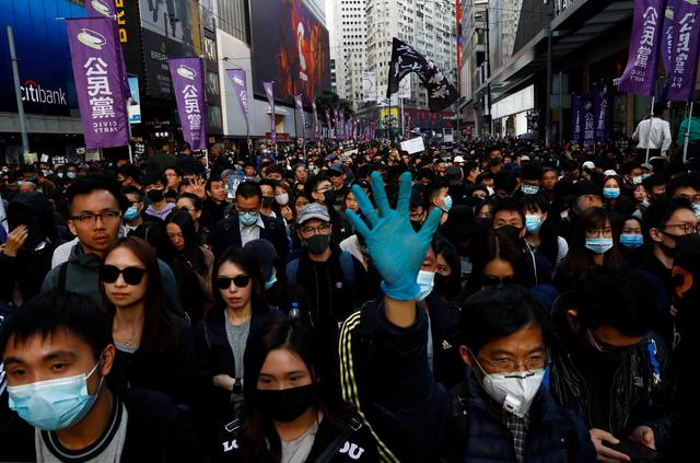 A protester holds up his hand, representing the five demands of the anti-government movement, during a Human Rights Day march, organised by the Civil Human Right Front, in Hong Kong, China December 8, 2019. REUTERS/Thomas Peter