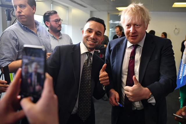 Britain's Prime Minister Boris Johnson poses for a photograph with a supporter at the Conservative Campaign Headquarters Call Centre in central London, Britain, December 8, 2019. Ben Stansall/Pool via REUTERS