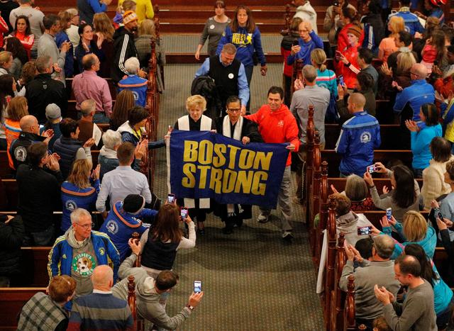 """FILE PHOTO: Boston Marathon bombing witness Carlos Arredondo carries a """"Boston Strong"""" banner after blessing the runners during services at Old South Church on the 5th anniversary of the Boston Marathon bombings in Boston, Massachusetts, U.S., April 15, 2018.   REUTERS/Brian Snyder"""