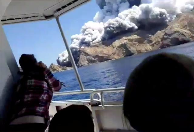 People on a boat react as smoke billows from the volcanic eruption of Whakaari, also known as White Island, New Zealand December 9, 2019 in this picture grab obtained from a social media video. INSTAGRAM @ALLESSANDROKAUFFMANN/via REUTERS