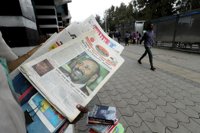 FILE PHOTO: A Vendor sales a news paper with a picture of Ethiopia's Prime Minister, Abiy Ahmed on it's cover in Addis Ababa, Ethiopia, December 10, 2019. REUTERS/Tiksa Negeri