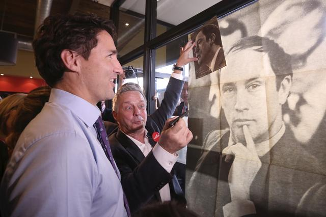 FILE PHOTO: Liberal leader Justin Trudeau looks at a poster of his late father, former Prime Minister Pierre Trudeau, during a campaign stop at a coffee shop in Sainte-Therese, Quebec, October 15, 2015. REUTERS/Chris Wattie/File Photo