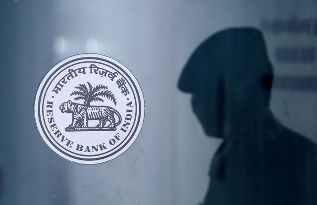 FILE PHOTO: A security guard's reflection is seen next to the logo of the Reserve Bank Of India (RBI) at the RBI headquarters in Mumbai, India, June 6, 2019. REUTERS/Francis Mascarenhas