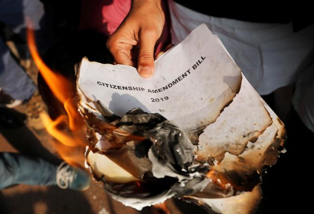 Demonstrators burn copies of Citizenship Amendment Bill, a bill that seeks to give citizenship to religious minorities persecuted in neighbouring Muslim countries, during a protest in New Delhi, India, December 11, 2019. REUTERS/Adnan Abidi