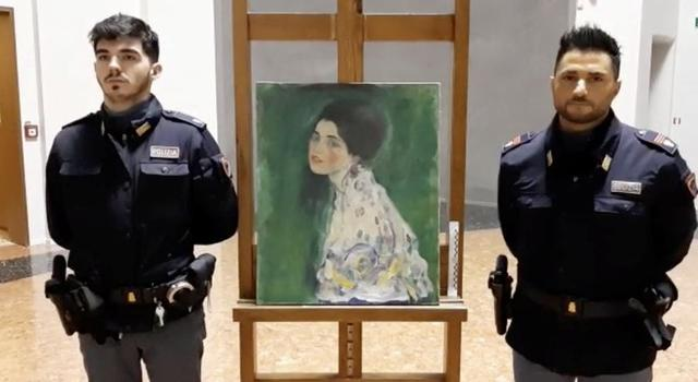 """Italian police stand next to what they say is a masterpiece by Austrian artist Gustav Klimt """"Portrait of a Lady"""" that was stolen in 1997 and was found hidden in an outside wall of an Italian gallery, in Piazcenza, Italy December 10, 2019 in this still image taken from a video. Polizia di Stato/Handout via REUTERS"""