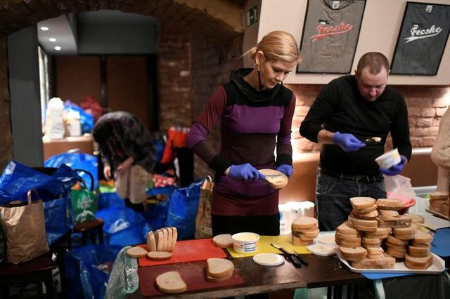 Volunteers of Budapest Bike Maffia, a Hungarian civil organization of biking fans who help the poor and homeless, make sandwiches to be distributed by bike in Budapest, Hungary December 10, 2019. REUTERS/Tamas Kaszas