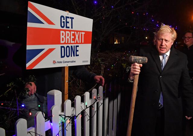 """Britain's Prime Minister and Conservative party leader Boris Johnson poses with a sledgehammer, after hammering a """"Get Brexit Done"""" sign into the garden of a supporter, in South Benfleet, Britain December 11, 2019. Ben Stansall/Pool via REUTERS"""