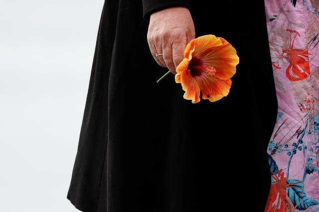 A woman holds a flower at a memorial at the harbour in Whakatane, following the White Island volcano eruption in New Zealand, December 11, 2019. REUTERS/Jorge Silva. Picture taken December 11, 2019. REUTERS/Jorge Silva