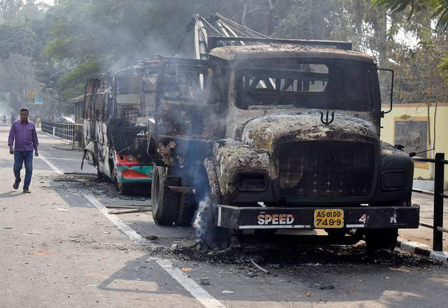 A man walks past damaged vehicles that were set on fire by demonstrators, during a protest after India's parliament passed Citizenship Amendment Bill, in Guwahati, India December 12, 2019. REUTERS/Anuwar Hazarika