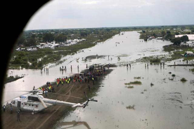 FILE PHOTO: A WFP (World Food Program) helicopter is seen on the flooded airstrip, after heavy rains and floods forced hundreds of thousands of people to leave their homes, in the town of Pibor, Boma state, South Sudan, November 6, 2019. REUTERS/Andreea Campeanu
