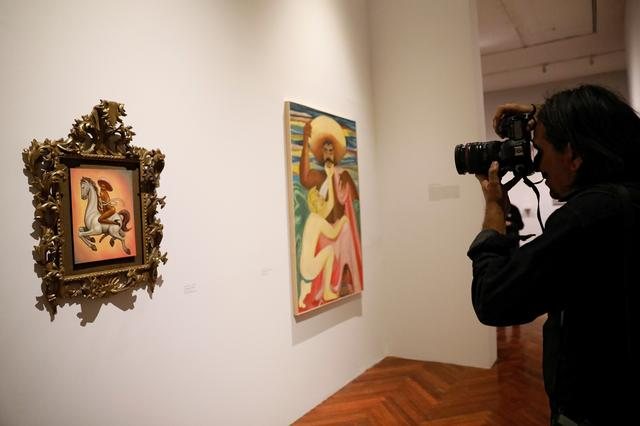 A photographer takes a picture of a painting by artist Fabian Chairez showing Mexican revolutionary hero Emiliano Zapata nude while wearing high heels and riding a horse, at the Fine Arts Palace in Mexico City, Mexico December 10, 2019. Picture taken December 10, 2019. REUTERS/Carlos Jasso NO RESALES. NO ARCHIVES