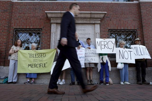FILE PHOTO: A pedestrian walks past death penalty protesters before the formal sentencing of convicted Boston Marathon bomber Dzhokhar Tsarnaev at the federal courthouse in Boston, Massachusetts June 24, 2015. REUTERS/Dominick Reuter/File Photo