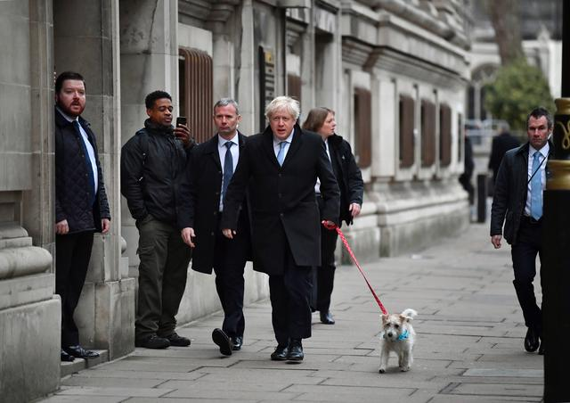 Britain's Prime Minister Boris Johnson walks with his dog Dilyn as he arrives at a polling station, at the Methodist Central Hall, after voting in the general election in London, Britain, December 12, 2019. REUTERS/Dylan Martinez