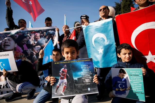 """Ethnic Uighur boys hold placards with the images of English soccer club Arsenal's midfielder Mesut Ozil during a protest against China in Istanbul, Turkey December 14, 2019. The placard reads: """"Thank you, Mesut Ozil, on behalf of 35 million oppressed"""".  REUTERS/Kemal Aslan"""