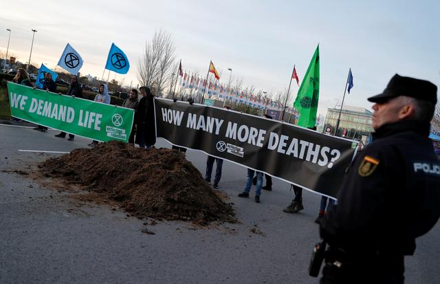 Climate change activists of Extinction Rebellion hold banners after unloading a truck filled with horse excrements in front of U.N. Climate Change Conference (COP25) in Madrid, Spain, December 14, 2019. REUTERS/Nacho Doce