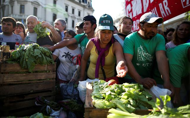 FILE PHOTO: People grab lettuce during a farmers' protest against low prices outside the Casa Rosada Presidential Palace in Buenos Aires, Argentina, February 27, 2019. REUTERS/Agustin Marcarian/File Photo